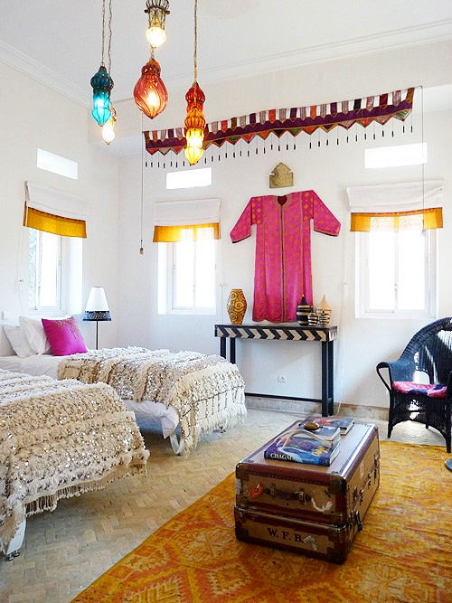 Between the Moroccan wedding quilts, trunk, geometric rug, punchy color, multiple light fixtures, I adore this space!