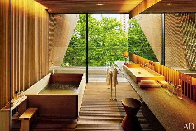 a guest bath clad in wooden slats and with a striking window wall that lends the feeling of a tree house. The rectangular tub and basin are made of hiba wood and are offset by a sculptural stool.