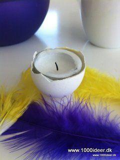 En fin påskeide er at anvende æggeskaller til fyrfadslys fx på påskebordet eller i påske blomsterdekorationen. Det kan være svært at få selve æggeskallen med fyrfadslys til at stå lige på bordet, men så kan man fx sætte en lille plastikring under. Her er der anvendt en plastikdims der er faldet af en puf. Alternativt skær en ring af køkkenrullepappet og beklæd dem med fx en serviet eller gult papir, garn eller andet. Vi har lagt nogle fjer om omkring for at få endnu mere påske over ideen.