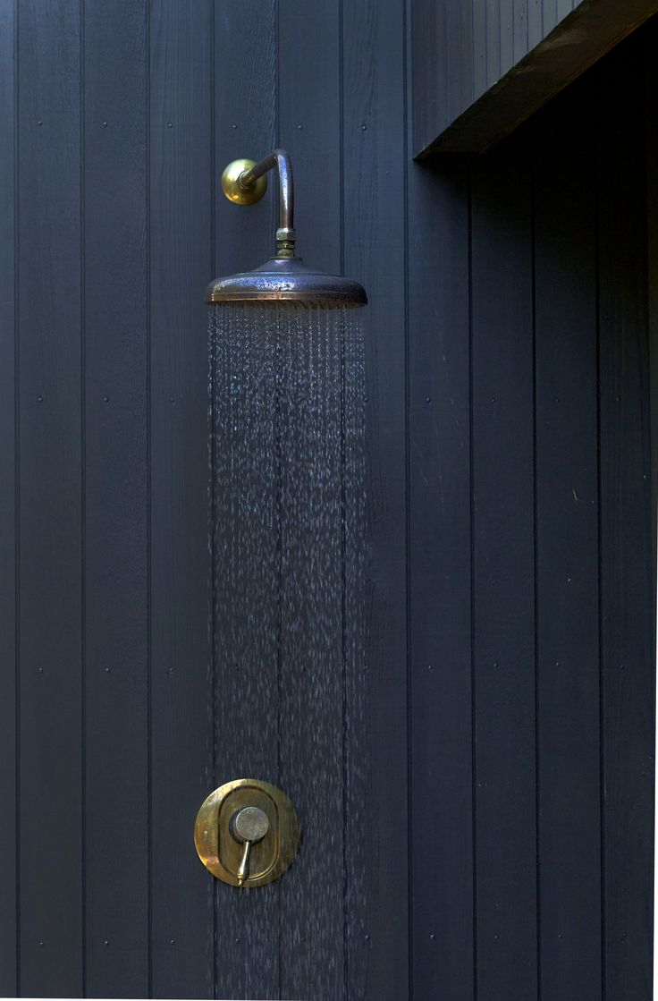 Black cedar cladding with beautiful antique brass finish outdoor shower by babylongardens.co.nz