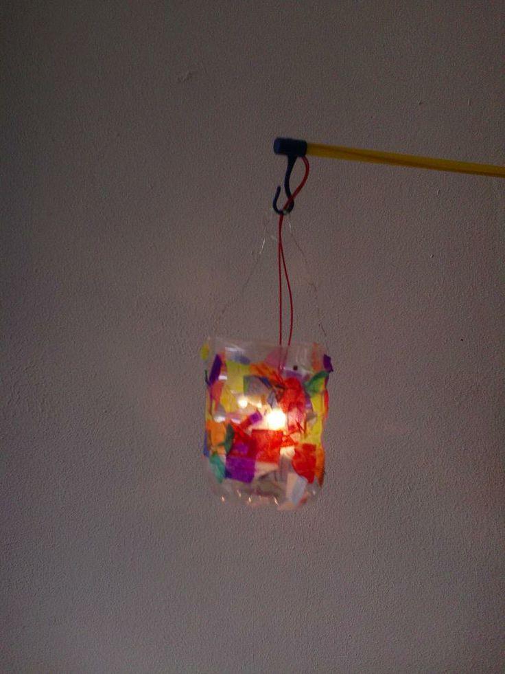Lampion van de onderkant van een lege fles, beplakt met snippers papier.