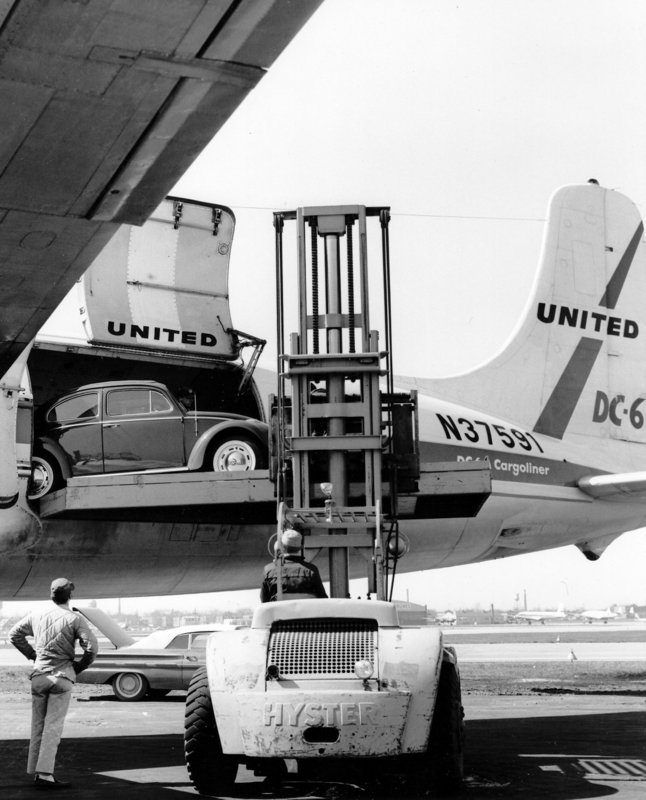 "Hyster fork-truck unloading VW bug at Chicago Midway in the late 50's. ""Put it in my trunk!"" the guy on the left says to the fork-truck operator. ""They'll never miss it and if they do, say it was probably stolen in Boston on the way over."""