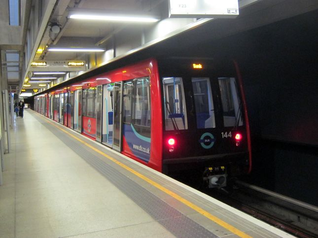 Docklands Light Railway 144 coupled with 115 waiting to depart en route to Bank from the subterranean south-east London terminus at Woolwich Arsenal