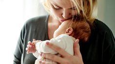 Das Bild zeigt eine Mutter, die ihr Baby hält.