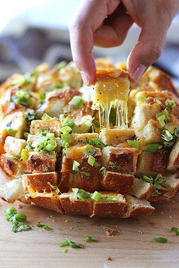 パンの切り込みに、チーズを挟んで作る「ブルーミング・オニオンブレッド」は海外で人気のメニュー。 お花のように華やかで、つまみやすいのでパーティにもぴったり!ご紹介するレシピはチェダーチーズを使っていますが、モッツァレラチーズを使っても美味しいです。ネギやゴマをトッピングしたり、バジルなどのハーブでアレンジしても◎