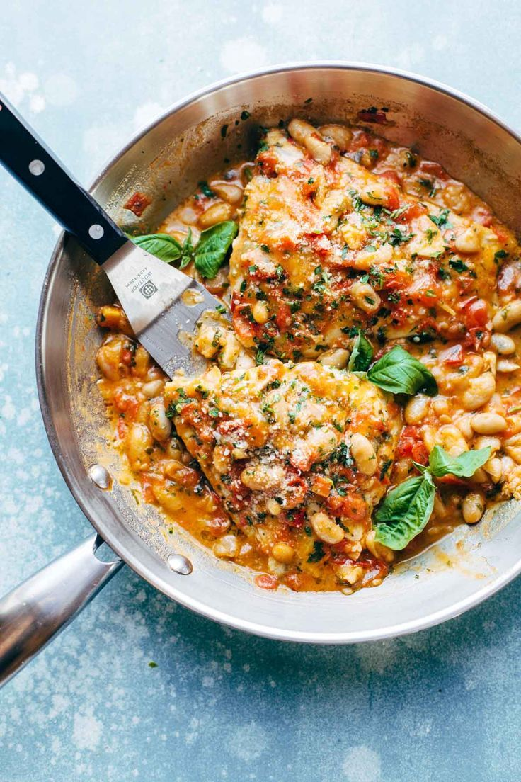 Garlic Basil Barramundi Skillet with Tomato Butter Sauce! SO YUMMY and super easy, with basic ingredients like garlic, basil, tomatoes, white beans, Parmesan, and white fish. Perfect with a green salad and crusty bread.. | pinchofyum.com