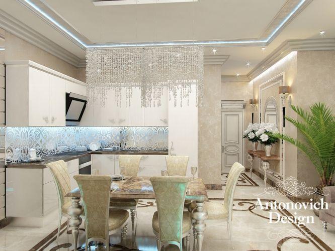 Светлая кухня в стиле арт-деко - стильная хрустальная люстра, мраморный пол с узорами, светлая кухонная мебель и изящные стулья. Здесь светло и тепло.