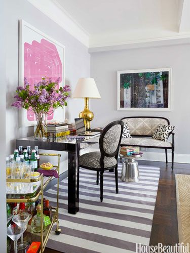 One end of the living room is defined by a Madeline Weinrib rug; When entertaining, the desk is used as a dining table.