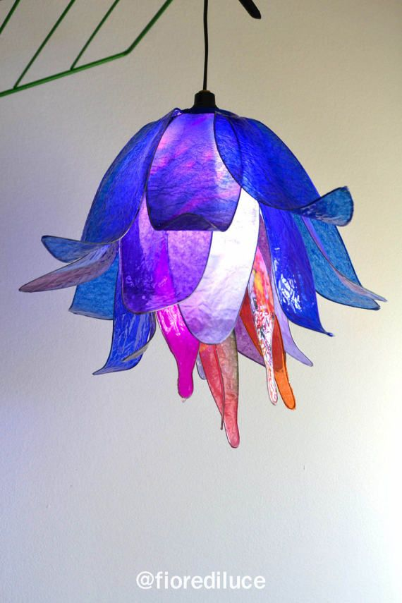 Un bellissimo lampadario a forma di bocciolo, sui toni del viola blu, colori notturni e con unesplosione di colori caldi nel centro della lampada, crea un angolo davvero suggestivo! interamente realizzata a mano, con lutilizzo di resine che asciugandosi creano leffetto vetrificato, solido robusto è possibile pulirlo con uno straccetto umido. Come tutte le nostre lampade è un pezzo unico! La lampada che vedete è subito pronta per essere spedita, è stata montata su un cavo elettrico provvisto…