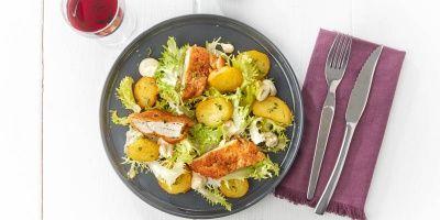 Gebakken aardappelschijfjes en gepaneerde kip op een bedje sla | Carrefour market