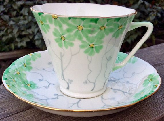 *****Shipping costs are extra (buyer pays).Shipping quotes are estimates only. Email us with your zip/postal code before making any purchase so that we can provide a more accurate quote*****  This is such a pretty Handpainted Grafto teacup and saucer in the Art Deco style. Crisp white background adorned with pale green flowers on grey vines. Rimmed in gold for that special touch. Mint vintage condition with no chips, cracks, crazing or repairs. Please examine the item with the zoom lens ...