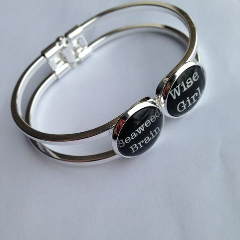 """This bracelet is part of our """"Geek Love"""" set.  It features images that read """"Seaweed Brain"""" and """"Wise Girl"""" from my family's favorite book series:  Percy Jackson.    The images are 16mm in size sealed under a glass dome and the bracelet has a hinged back opening.  I can make any of our tie cl..."""