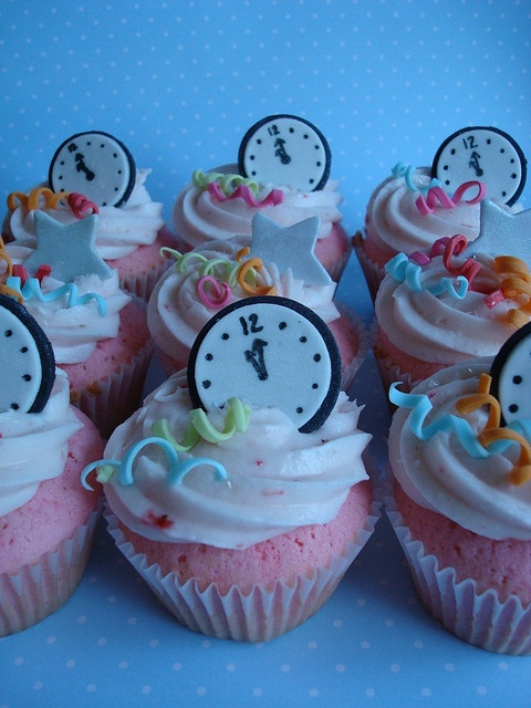 New Year's confetti, stars and clocks on top of pink champagne cake and strawberry champagne buttercream