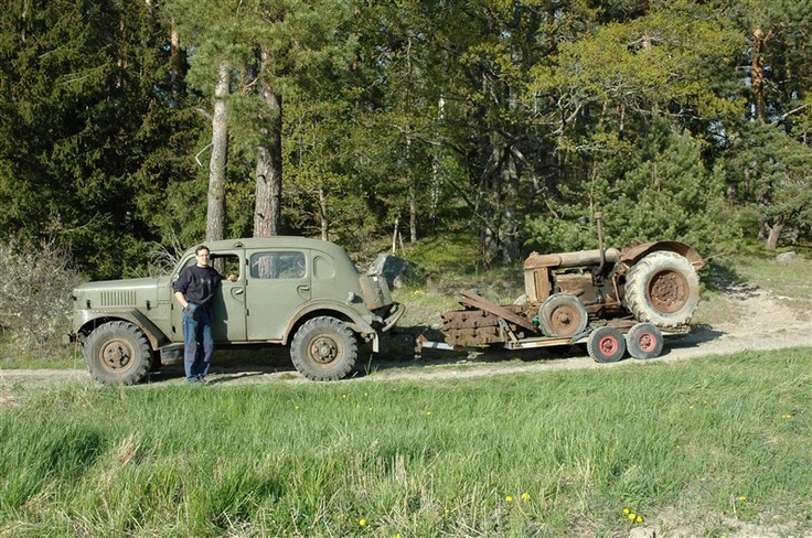 Old tractor towed by awesome Volvo Sugga military 4x4. Those tires are huge!