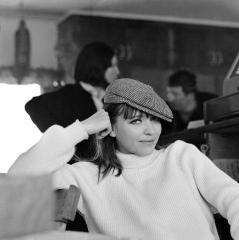 """L'attrice Anna Karina con coppola e dolcevita. La corrente cinematografica Nouvelle Vague lancia lo stile """"tom boy"""" e per la prima volta la donna si rivela indipendente, ironica e scanzonata. Ma attitude da ragazzino e abbigliamento maschile risaltano ancora di più femminilità e sex appeal."""