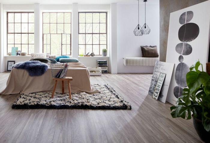 laminat bodenbelag schlafzimmer doppelbett musterteppich holzhocker pflanze wandbilder spruch radiator blaue kissen