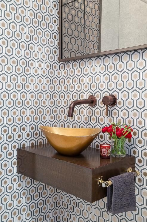 Brown finished floating vanity is fitted with a glass and brass towel rack, a brass vessel sink, and a faucet mounted on a wall covered in David Hicks Hexagon Wallpaper under a gray framed vanity mirror.