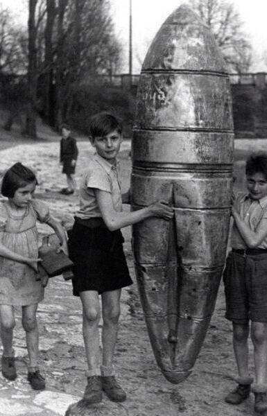 Los niños juegan con la cáscara de una bomba caída. Berlín, Segunda Guerra Mundial.