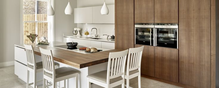 Walnut & Cornforth White Kitchen A contemporary kitchen design contrasting an understated, neutral white finish with rich American Black Walnut. The practical yet stunning Cararra composite work-surfaces compliment the minimalist style of the sleek handle-less kitchen island and wall cabinets, finished in 'Cornforth White'