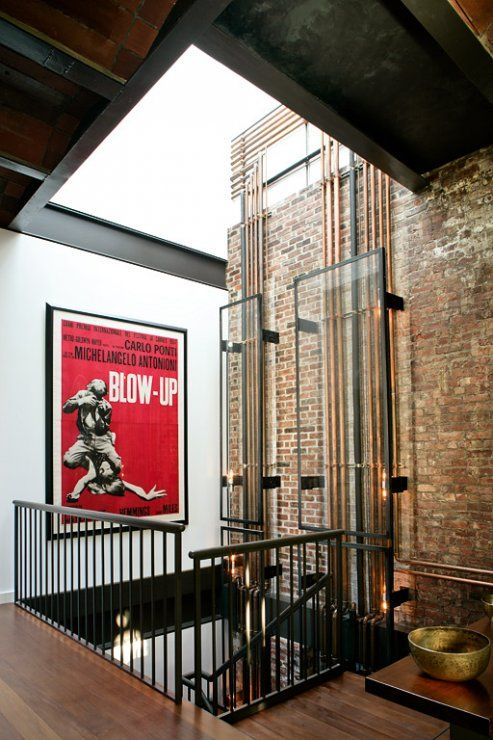 Industrial Interiors That Features Open Pipes With Natural Stone Wall And Black Stairs Chandelier And Table With Hardwood Flooring