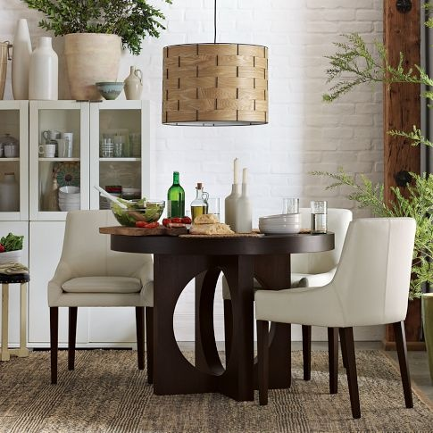 I love this round dining table. And the white buffet. And the white brick wall. And all the plants. - West Elm
