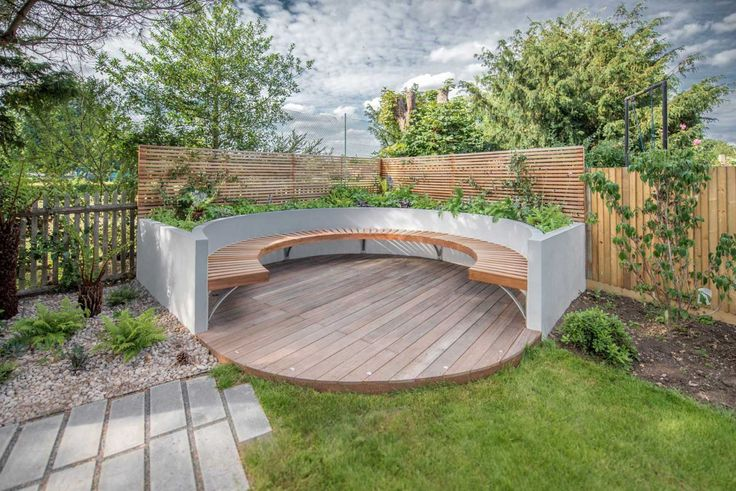 Circular deck with bench set within raised bed. Part of garden design in Dulwich