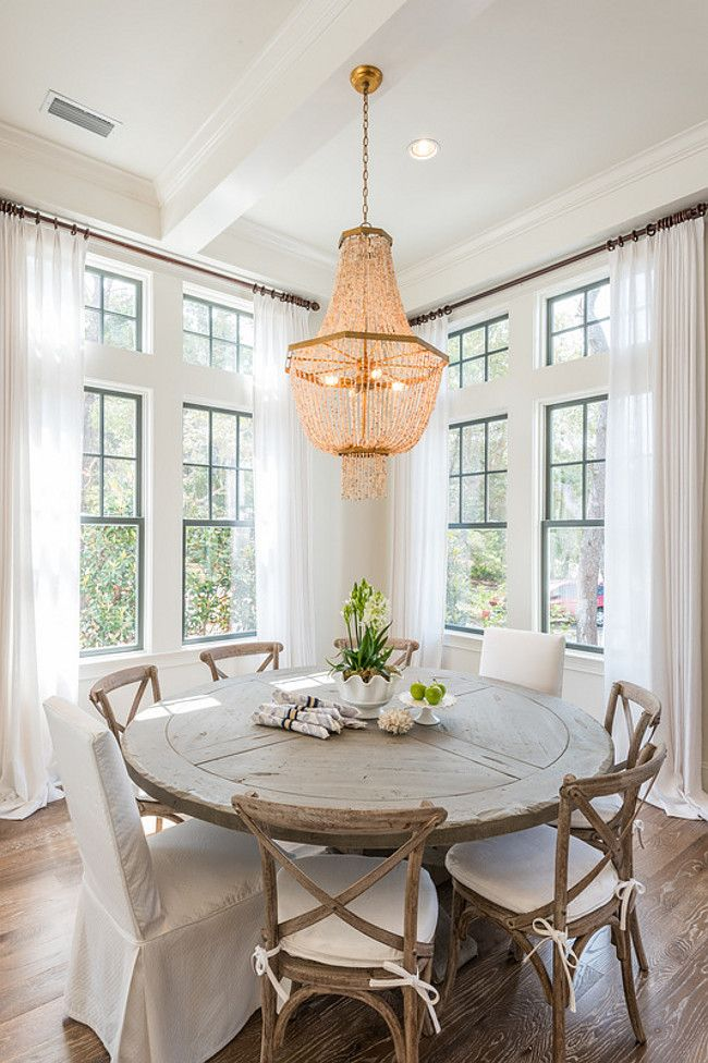 Dining room features a gold beaded chandelier hanging over a round salvaged wood dining table lined with French cafe chairs and white slipper chairs placed in front of windows dressed in white drapery panels. Old Seagrove Homes.