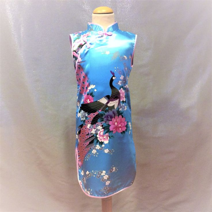 Turquoise Chinese jurk met knoopsluiting schuin onder de hals. Smal model van 100% polyester zonder stretch.  Model: Meilan