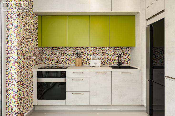 """Contrabalansând efectul culorilor și rotunjimea bulinelor de pe tapet, frontul mobilierului are un aspect curat, cu un efect texturat de piatră albă, precum și linii riguroase, clar delimitate.  Puteți alege din 50 de modele de bucătării sau să vă """"jucați"""" cu peste 180 de variante de fronturi disponbile în portofoliul Kuxa: https://kuxa.ro/fronturi-bucatarii"""