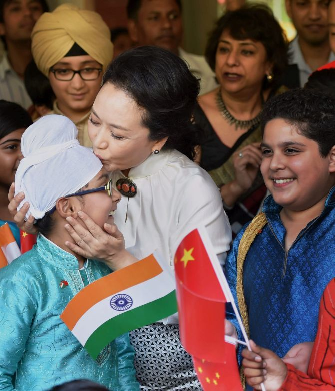 Peng Liyuan kisses a student during her visit to Tagore International School