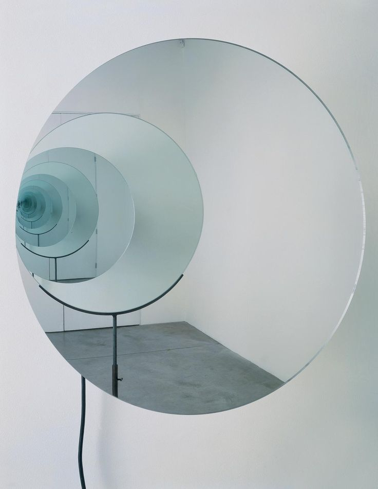 Artwork • Studio Olafur Eliasson  Hung at eye level on a wall, a mirror driven by a motor spins rapidly. Mounted on a tripod across from the rotating mirror is another, static mirror. The construction of facing mirrors conjures a shimmering, infinite vortex.