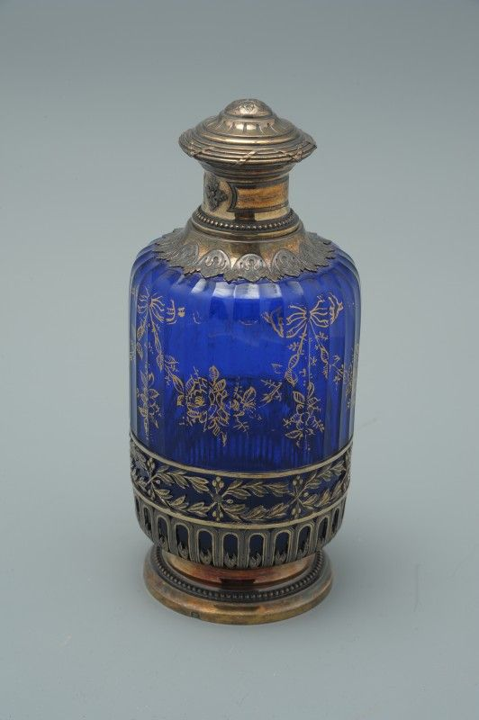A FRENCH SILVER CASED COBALT COLOGNE PERFUME BOTTLE Paneled cobalt blue glass with gold tracery and fitted with a gilded silver frame top and cover, glass stopper.Unknown maker's mark of GB.
