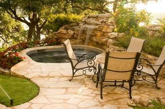 Beautiful rock waterfall flowing into an in-ground hot tub creates the perfect backyard oasis to soak your cares away.
