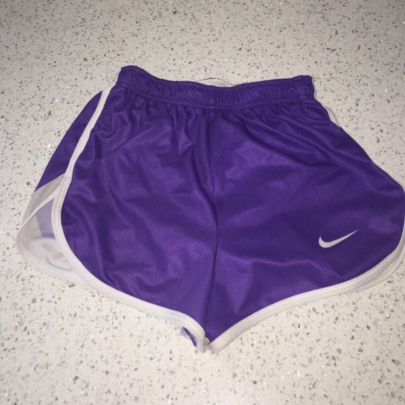 Nike running shorts purple gray color combo Purple/gray with white trim Nike running shorts. Liner inside (picture 3)  Slit detail on the sides. Lightweight material. I cut the tag out and took the drawstring out because I can't stand it when I run. Excellent condition otherwise no wear or tear. Adorable Nike running shorts with a lot of wear left in them. Size xs/small Nike Shorts