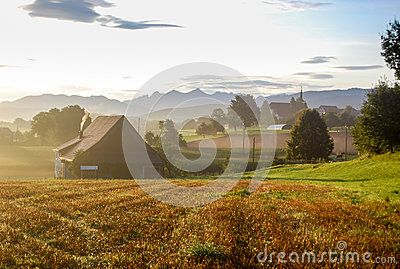 The sun is rising over a village in the Swiss Alps. Agricultural landscape with a field in the foreground, houses and a church in the back and mountains in the background.