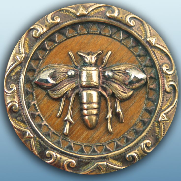 Antique brass bee button with wood background & cut steels.