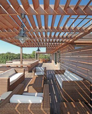 Grande terrasse semi ombragée avec pergola et salon de jardin en rotin