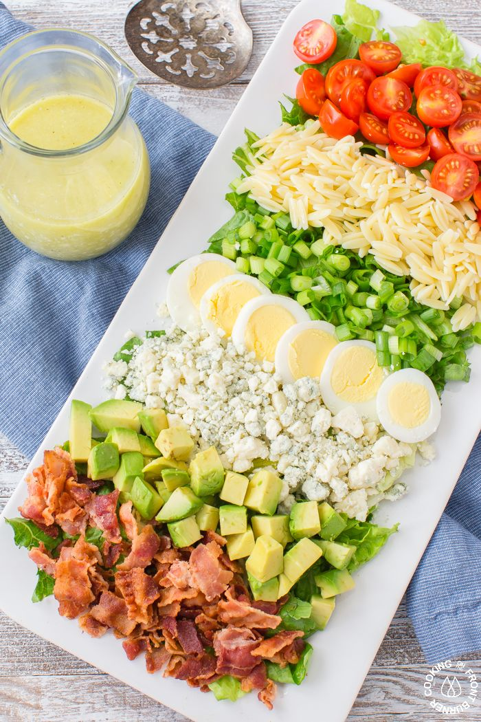 This Cobb Salad is a flavor explosion with crispy bacon, tangy blue cheese, fresh tomatoes, avocado, green onions, hard boiled eggs nestled on a bed of romaine lettuce and drizzled with an easy blue cheese vinaigrette. And in case you didn't notice, it has my favorite pasta to give it a unique twist!