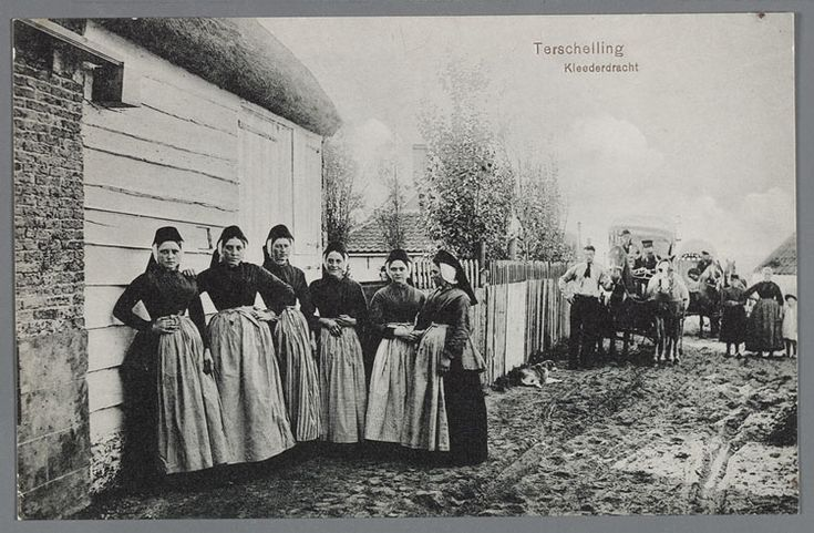 Zes vrouwen in klederdracht poseren op een onverharde weg. Aan de weg een hek als erfscheiding. Op de achtergrond staan twee opperîdwagens, elk getrokken door twee paarden. 1910-1940 Terschelling #Terschelling