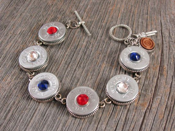 Red, White & Blue - Patriotic Themed 20 Gauge Silver Shotgun Casing Bracelet - A SureShot Jewelry Exclusive!  This great looking bracelet features six (6) silver Winchester or Remington brand 20 gauge shotgun shell casings, set in beaded edge bezels to finish the casings both front and back and to keep with our quality standards. Bracelet closes with a matching rope textured toggle clasp and comes with both our signature pistol charm and our signature jewelry tag.  We offer this bracelet…