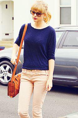 Huidskleurige broek. Blauw truitje met een oranje/bruine tas. Accessoires: Leuke bril.  Huidskleurige pants. Blue shirt with an orange/brown bag. Accessories: Nice glasses.
