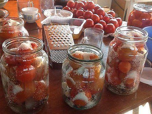 """Помидоры """"Царские"""" Поделюсь суперским рецептом засолки небольших помидор в литровые банки. 1) В стерилизованные баночки укладываем 1-2 зубчика чеснока, добавляем листик лаврушки. 2) Укладываем помидоры в банки. 3) Помидоры заливаем кипятком и накрываем крышками. 4) Дать настояться 15 минут. 5) Слить воду в кастрюлю и довести до кипения. 6) Пока вода закипает, в банки с помидорами кладем: 1 дес. Ложку соли, 2 дес. Ложки сахара, 4 горошка перца, на конце чайной ложки кладем кориандр и столько…"""