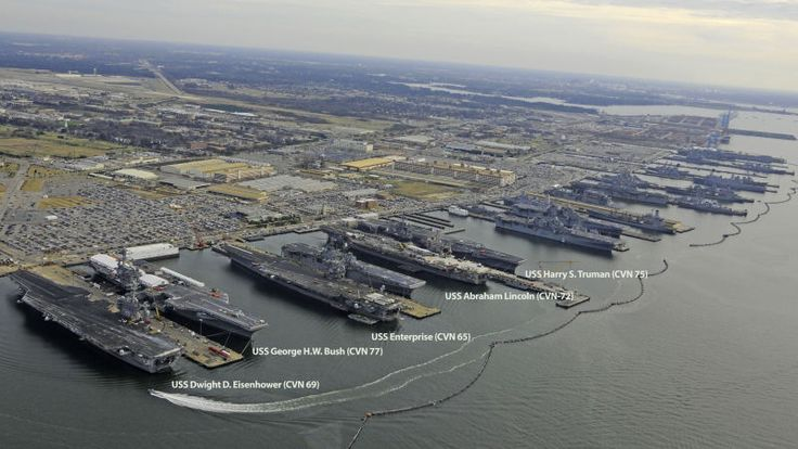 Here's a rare sight: four out of the ten Nimitz-class aircraft carriers—the largest warships ever built—plus an Enterprise-class carrier docked together. They are resting at Naval Station Norfolk, Virginia, which coincidentally is the largest naval base in the world. Look at all that engineering and firepower. And it's only half of the Nimitz fleet!