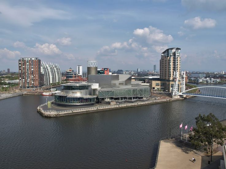 "From the top of the The Imperial War Museum North, on Trafford Wharf Road, Salford Quays, Manchester, England, designed by architect Daniel Libeskind (1946). In the middle at the water The Lowry Theatre, designed by the architects James Stirling (1926-1992) and Michael Wilford (1938). At the right the Millennium Lift Bridge, designed by Carlos Fernández Casad, and the residential tower ""Imperial Point"" and the Lowry Outlet Mall, together The Lowry Galleria, designed by DLA Design."