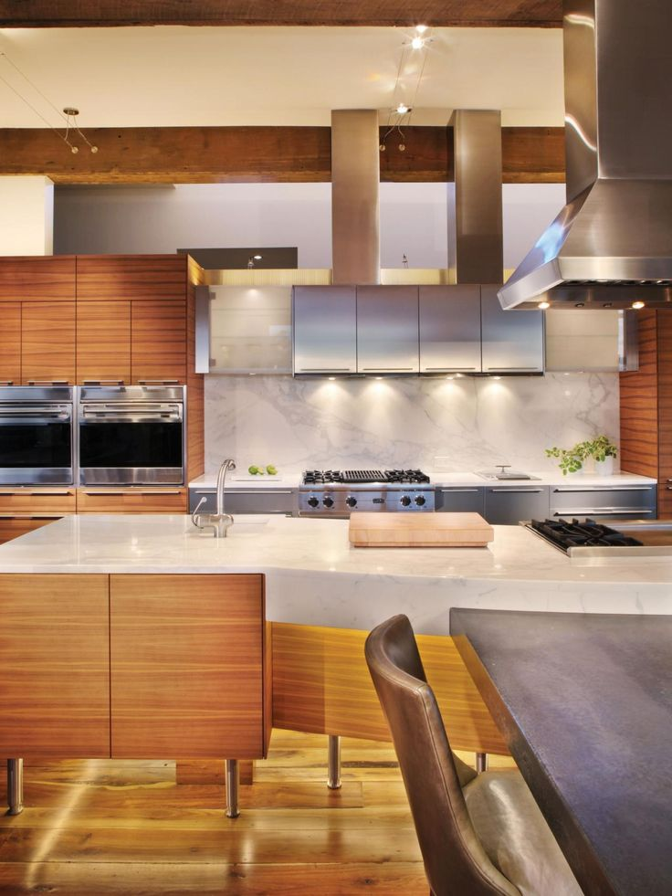 Shimmering surfaces, shining fixtures, high-sheen finishes, and perfectly placed lighting accents are a prominent personality trait of current kitchens. This kitchen is a fine composition of stainless steel, walnut wood veneer, and light reflecting off a vast Calcutta gold marble island top. Lights dotting the floor at the base of the island create a soft glow along the recessed toe-kick. Wood floors appear to glow with the shine of time-worn care and polishing. However, it's the sheen and…