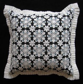 "DAISY EYELET --- Black/ecru embroidered eyelet daisy pattern w/ viking blue corduroy lining.  Ecru grosgrain boxpleat trim.  Awning striped yarn dye back w/ patent obi and grosgrain ribbon tie. 100% cotton eyelet front – 100% cotton corduroy lining – poly/rayon yarn dye back.  Size: 18"" x 18"" Style #: 1041016"