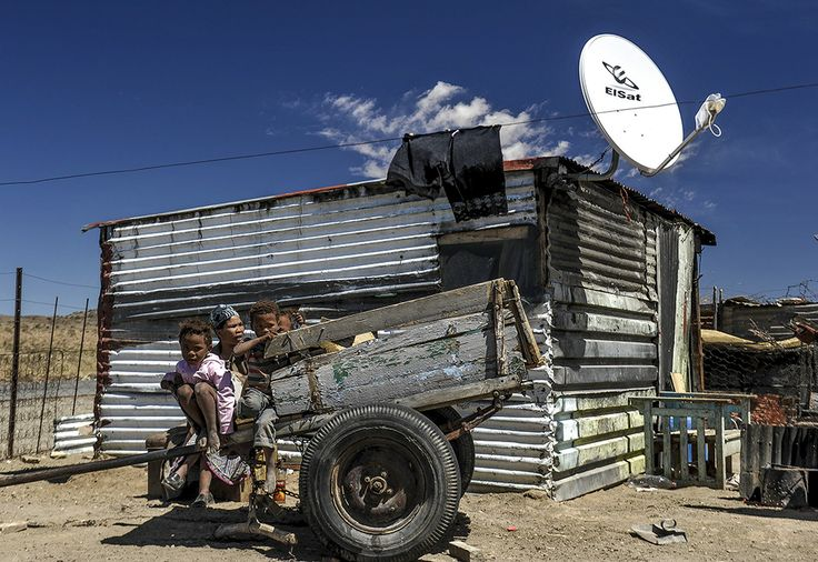 Children sit upon the iconic donkey cart, which defines their way of life. But the satellite dish behind shows how they are rapidly joining the outside world.