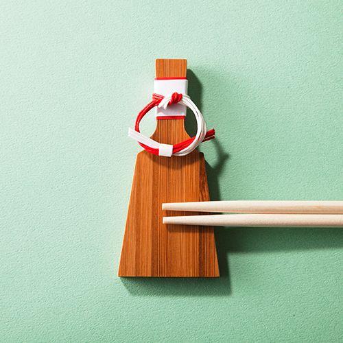 """【公長齋小菅】羽子板水引付箸置き 新年の食卓にふさわしい、水引付きの羽子板型箸置き 1898年の創業以来、竹工芸を一貫して扱い、製品を皇室にも納めてきた歴史と実績を持つ「公長齋小菅(こうちょうさいこすが)」。""""伝統とは革新の連続である""""という信条のもと、現代の生活に合ったアイテムを提案すべく常に竹工芸の価値を高めるための挑戦をし続けるブランドだ。「羽子板水引付箸置き」はその名の通り、羽子板のかたちをした箸置き。慶事の象徴・竹でできており、しっかりと分厚い質感が頼もしい。また上部の水引が祝いの場にふさわしくありつつも、どこかチャーミン グな味わいも醸し出している。正月に使う箸は「祝い箸」と呼ばれ、端がどちらも同じ形状をしている。これは片方を人間が、もう片方は歳神様が使うとされているから。そんな箸のエピソードとともに、新年の食事を楽しみたい。"""