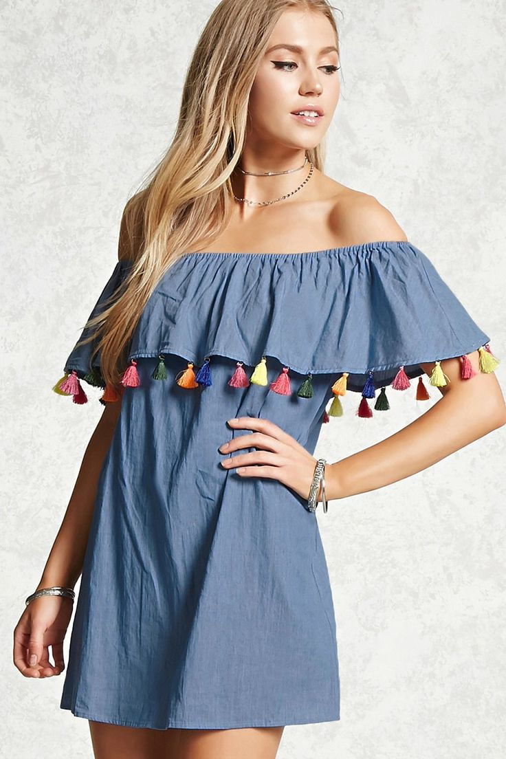 A chambray dress featuring an elasticized off-the-shoulder neckline, a flounce layer, colorful tassel trim, short sleeves, and a mini silhouette.