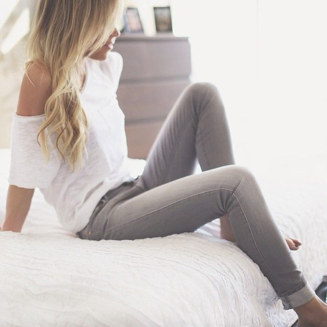 faded light grey skinny jeans cuffed at bottom and white loose oversized off the shoulder tshirt.